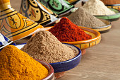 Diversity of Moroccan powder herbs in colorful ceramic tagines close up