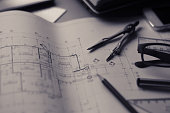 Divider, pencil, pen, ruler, glasses and smartphone and blueprint on table top.Table top view of Engineers table at office workplace.selective focus.Man hand point to blueprint.Black and white effect.