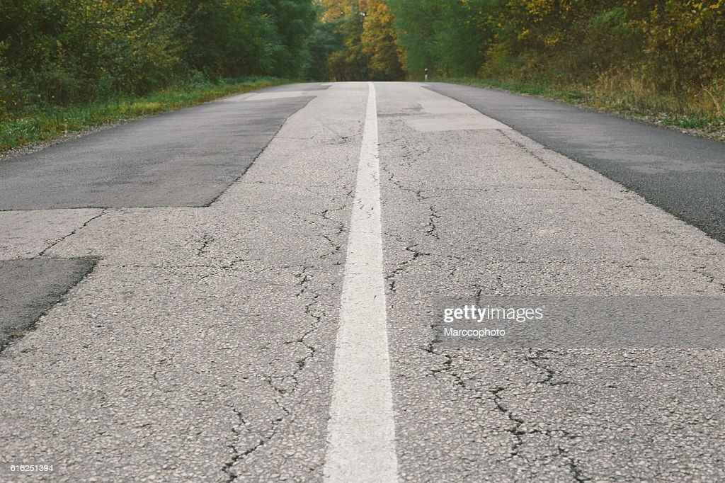 Dividing line on old cracked and patched asphalt road : Stock-Foto