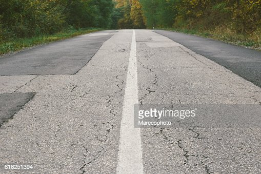 Dividing line on old cracked and patched asphalt road : Stock Photo