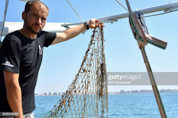 Diving captain for US NonGovernmental Organisation Sea Shepherd Manu shows a fishing net found in the Coulombray area near PalavasLesFlots during a...
