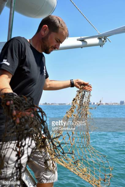 Diving captain for US NonGovernmental Organisation Sea Shepherd Manu collects and shows a fishing net found in the Coulombray area near...
