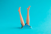 Doll legs coming out from blue paper background summer diving or drowning minimal creative concept.