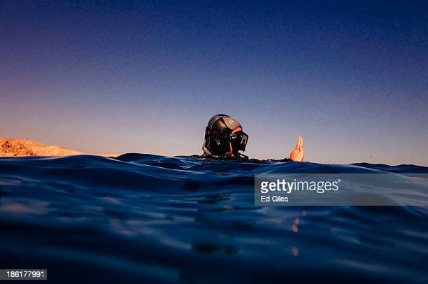 SCUBA diving guide signals to other divers in the water before beginning a dive during a guided trip on October 27 2013 at the Red Sea near the...