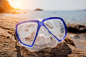 Diving mask at the beach splashed by waves