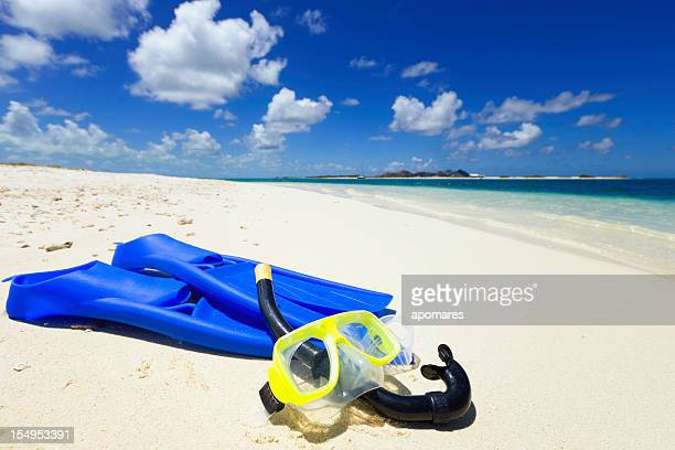 Diving mask, snorkel and fins on a tropical sand beach