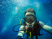 Young diver in the ocean, taking a selfie with blue water background.
