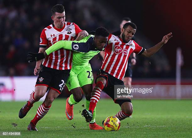 Divock Origi of Liverpool battles with PierreEmile Hojbjerg and Ryan Bertrand of Southampton during the EFL Cup semifinal first leg match between...