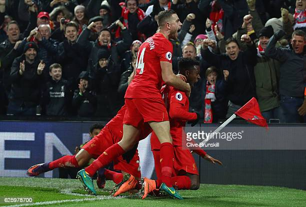 Divock Origi of Liverpool celebrates scoring the opening goal with his captain Jordan Henderson and his team mates during the Premier League match...