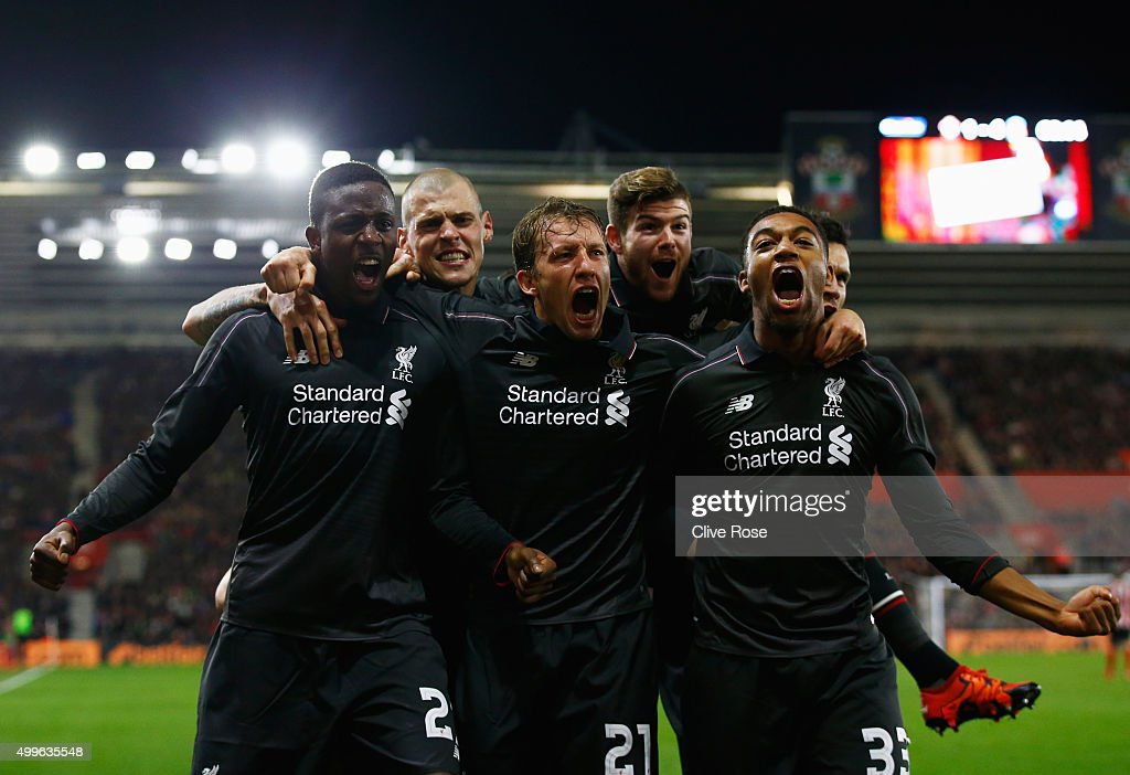 Divock Origi of Liverpool celebrates with team mates Lucas Leiva and Jordon Ibe as he scores their fourth goal during the Capital One Cup quarter...