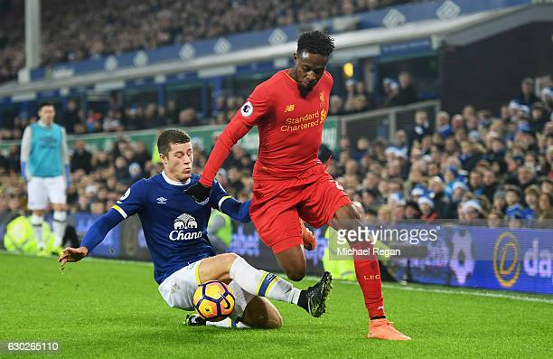 Divock Origi of Liverpool is challenged by Ross Barkley of Everton during the Premier League match between Everton and Liverpool at Goodison Park on...