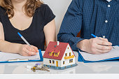 Divorce and dividing a property concept. Man and woman are signing divorce agreement.