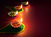 Colorful clay diya lamps lit during diwali celebration.