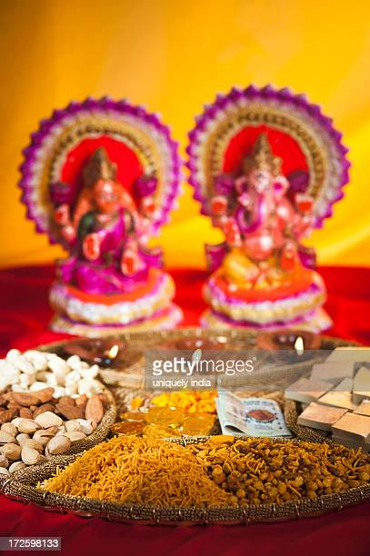 Diwali sweets and snacks in front of idols of Lakshmi and Ganesh during Diwali festival