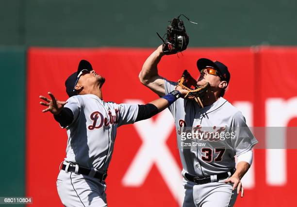 Dixon Machado and Jim Adduci of the Detroit Tigers go for a ball hit by Ryon Healy of the Oakland Athletics in the seventh inning at Oakland Alameda...