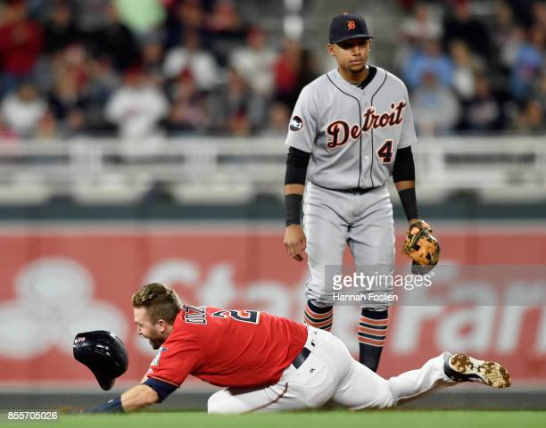 Dixon Machado of the Detroit Tigers looks on as Brian Dozier of the Minnesota Twins trips on his way to third base during the first inning of the...