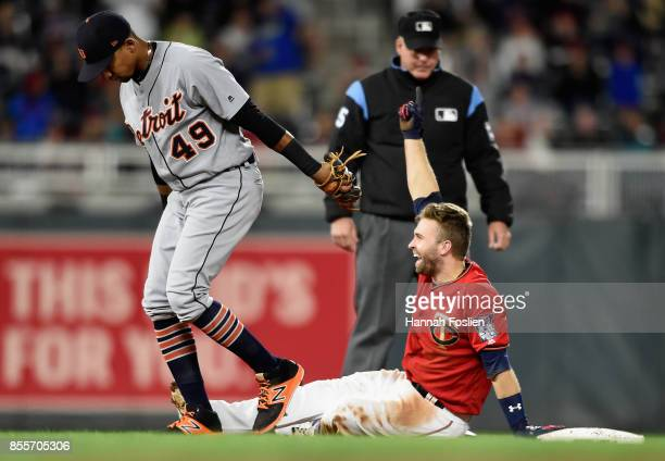 Dixon Machado of the Detroit Tigers reacts as Brian Dozier of the Minnesota Twins celebrates a double after tripping on his way to third base during...