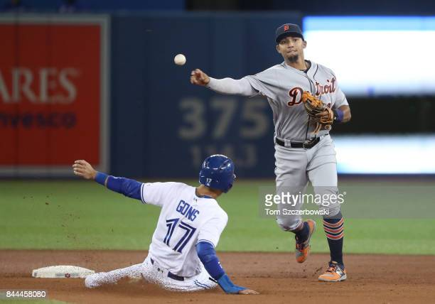 Dixon Machado of the Detroit Tigers turns a double play in the seventh inning during MLB game action as Ryan Goins of the Toronto Blue Jays slides...