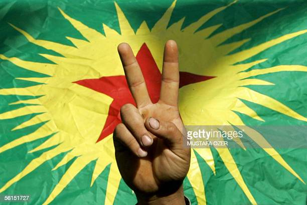 A demonstrator flashes a Vsign before outlawed PKK flag 13 November 2005 during the 'democracy and peace' demonstration organised by local...