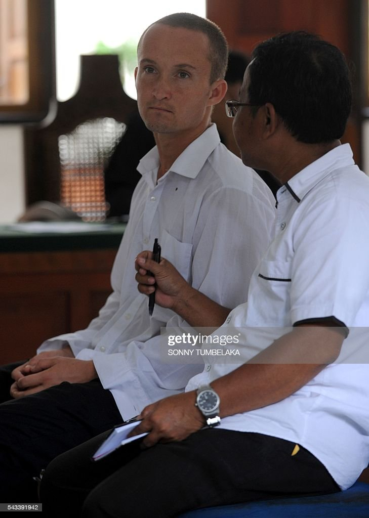 Djai Heijn of the Netherlands (C) listens to an interpreter during his drugs trial at a court in Denpasar, on Indonesia's resort island of Bali on June 28, 2016. The Indonesian prosecutor has recommended a 10-month prison sentence for Heijn, who was arrested by customs and police officers on January 11 for allegedly taking receipt of a package sent from Spain which contained 224 grams of marijuana. / AFP / SONNY