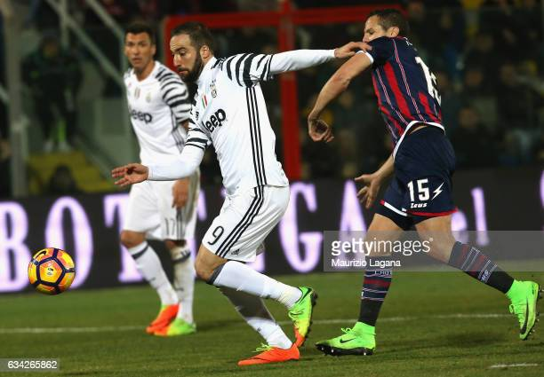Djamel Masbah of Crotone competes for the ball with Gonzalo Higuain of Juvents during the Serie A match between FC Crotone and Juventus FC at Stadio...