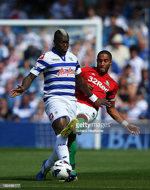Djibril Cisse of QPR is tackled by Ashley Williams of Swansea during the Barclays Premier League match between Queens Park Rangers and Swansea City...