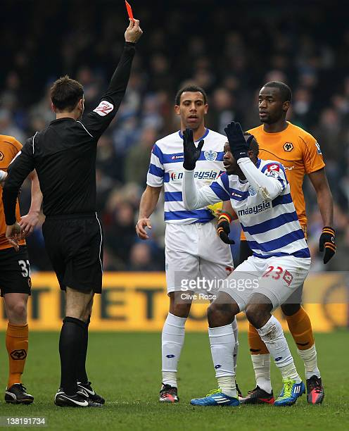 Djibril Cisse of Queens Park Rangers is shown a red card by referee Mark Clattenburg during the Barclays Premier League match between Queens Park...