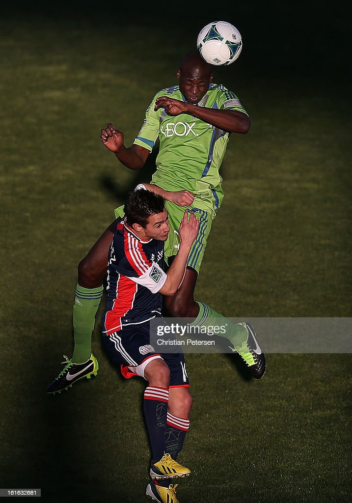 Djimi Traore #50 of the Seattle Sounders goes up for a header over Diego Fagundez #14 of the New England Revolution during the first half of the FC Tucson Desert Diamond Cup at Kino Sports Complex on February 13, 2013 in Tucson, Arizona.