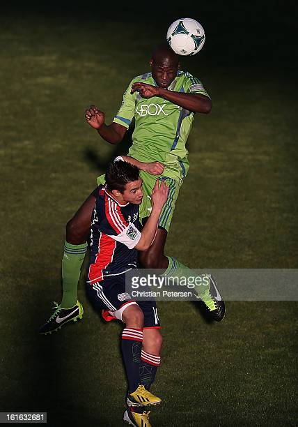 Djimi Traore of the Seattle Sounders goes up for a header over Diego Fagundez of the New England Revolution during the first half of the FC Tucson...