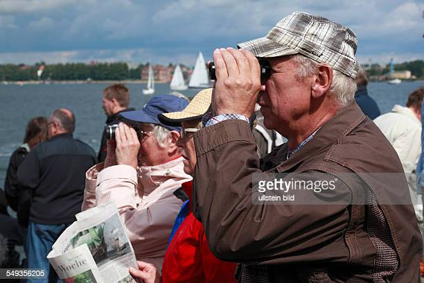 DKiel Kiel Fjord Baltic Sea SchleswigHolstein Kieler Woche 2011 sailing event windjammer parade spectators at the lakeshore older man and older woman...