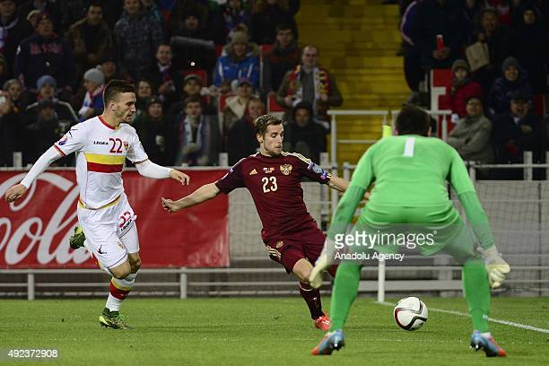Dmitri Kombarov of Russia vies with Marko Simic and Milan Mijatovic of Montenegro during the UEFA Euro 2016 qualifying round Group G football match...