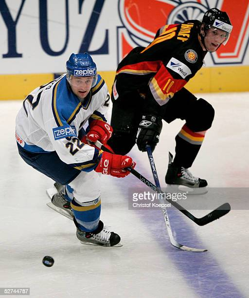 Dmitri Upper of Kazakhstan moves the puck against Christian Ehrhoff of Germany during the IIHF World Men's Championships preliminary round group D...