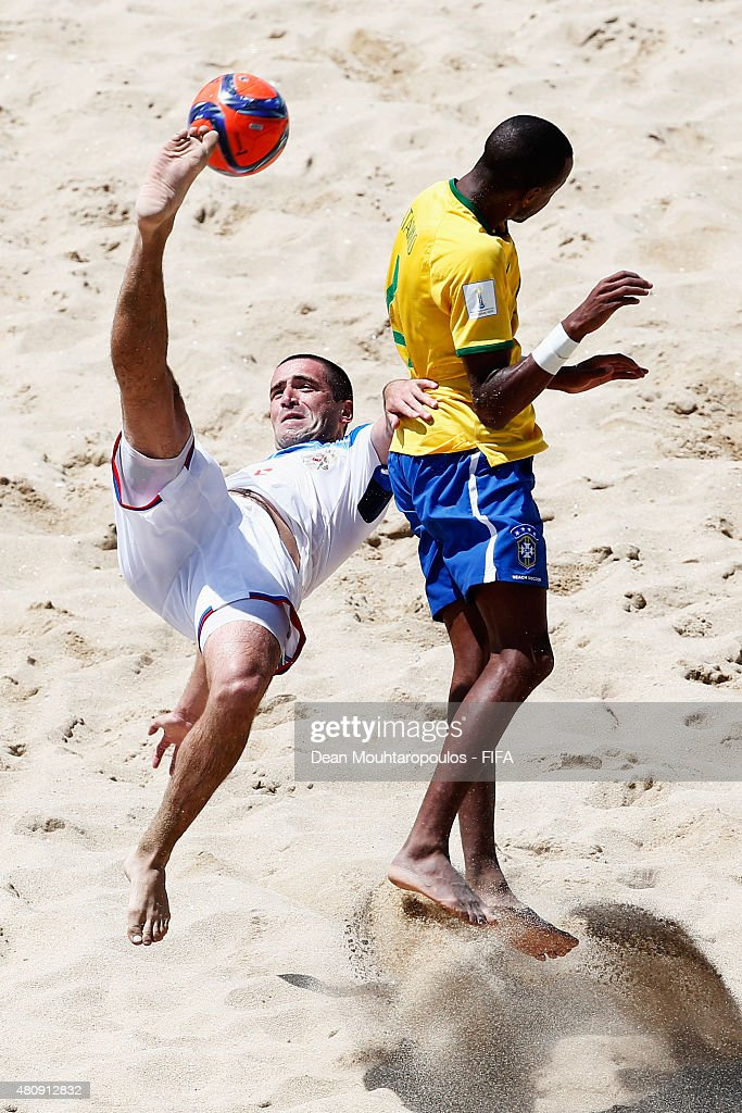 Dmitrii Shishin of Russia attempts a scissor kick shot on goal in front of Catarino of Brazil during the FIFA Beach Soccer World Cup quarter final match between Brazil and Russia held at Espinho Stadium on July 16, 2015 in Espinho, Portugal.