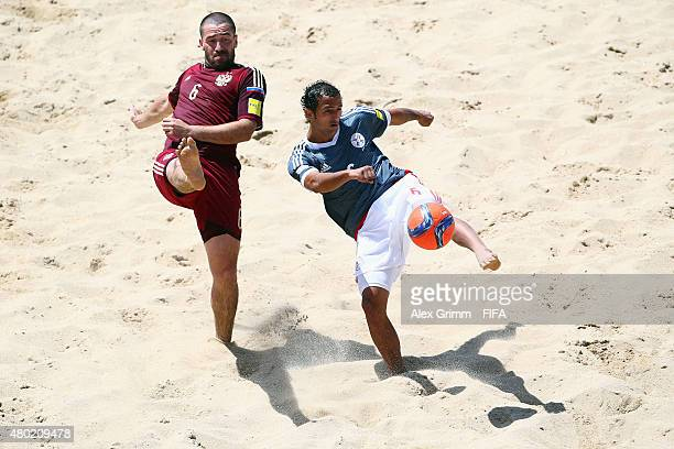 Dmitrii Shishin of Russia is challenged by Pedro Moran of Paraguay during the FIFA Beach Soccer World Cup Portugal 2015 Group D match between Russia...