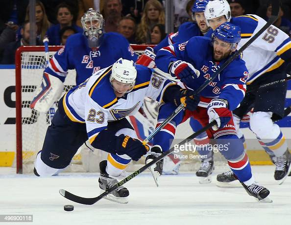 Dmitrij Jaskin of the St Louis Blues and Jarret Stoll of the New York Rangers battle for the puck during the second period at Madison Square Garden...