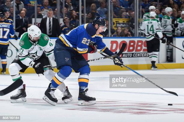 Dmitrij Jaskin of the St Louis Blues handles the puck as Alexander Radulov of the Dallas Stars pressures at Scottrade Center on October 7 2017 in St...