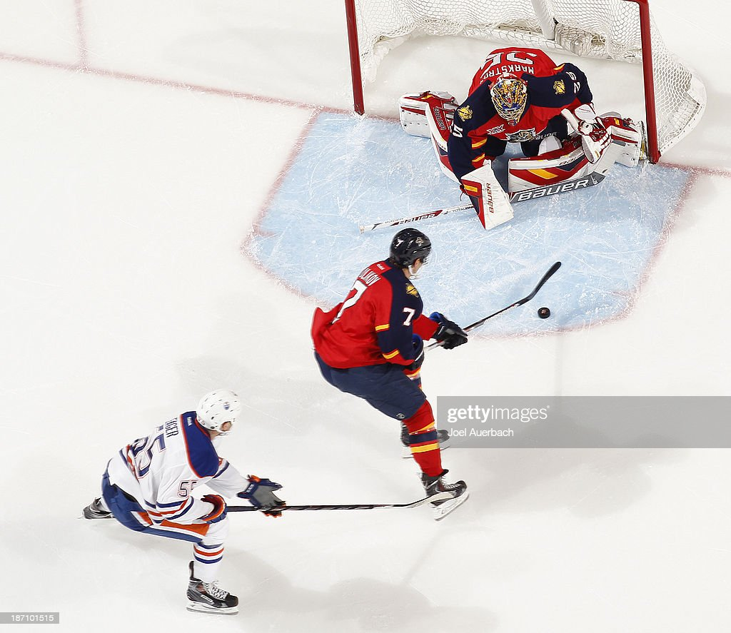 Dmitry Kulikov #7 clears the puck from in front of goaltender Jacob Markstrom #25 of the Florida Panthers as Ben Eager #55 of the Edmonton Oilers trails the play at the BB&T Center on November 5, 2013 in Sunrise, Florida. The Oilers defeated the Panthers 4-3 in overtime.