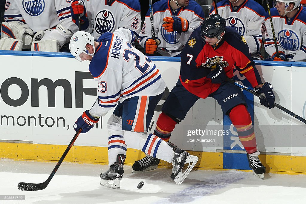 Dmitry Kulikov #7 of the Florida Panthers and Matt Hendricks #23 of the Edmonton Oilers battle along the boards for control of the puck during third period action at the BB&T Center on January 18, 2016 in Sunrise, Florida. The Oilers defeated the Panthers 4-2.