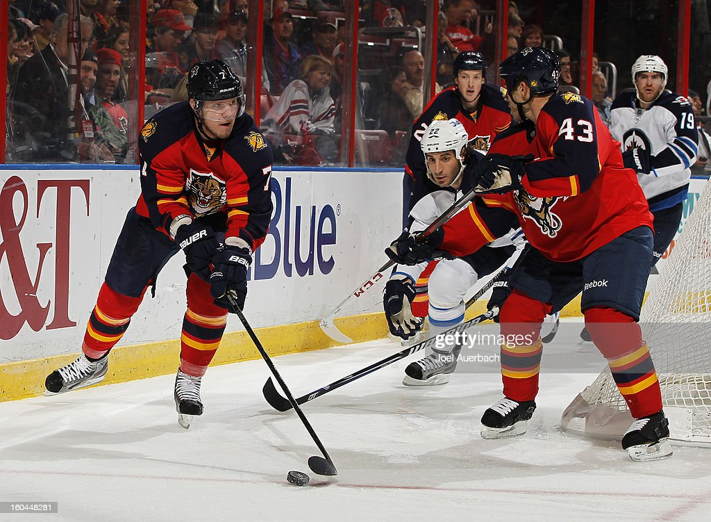 Dmitry Kulikov #7 of the Florida Panthers clears the puck as <a gi-track='captionPersonalityLinkClicked' href=/galleries/search?phrase=Chris+Thorburn&family=editorial&specificpeople=2222066 ng-click='$event.stopPropagation()'>Chris Thorburn</a> #22 of the Winnipeg Jets attempts to reach it at the BB&T Center on January 31, 2013 in Sunrise, Florida. The Panthers defeated the Jets 6-3.