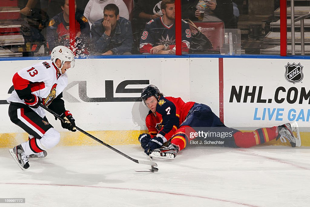 Dmitry Kulikov #7 of the Florida Panthers digs the puck out from the boards against Peter Regin #13 of the Ottawa Senators at the BB&T Center on January 24, 2013 in Sunrise, Florida.