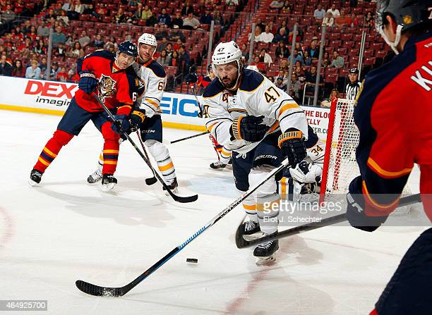 Dmitry Kulikov of the Florida Panthers passes to teammate Jaromir Jagr while Zach Bogosian and Andre Benoit of the Buffalo Sabres defend at the BBT...