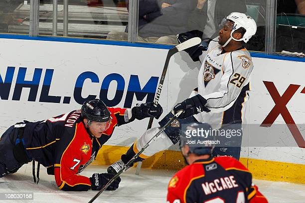 Dmitry Kulikov of the Florida Panthers receives a tripping penalty after taking Joel Ward of the Nashville Predators to the ice on January 13 2011 at...