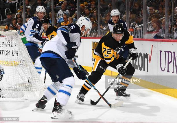 Dmitry Kulikov of the Winnipeg Jets and Patric Hornqvist of the Pittsburgh Penguins battle for the loose puck at PPG Paints Arena on October 26 2017...