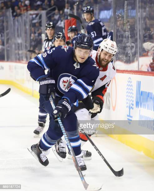 Dmitry Kulikov of the Winnipeg Jets plays the puck away from Zack Smith of the Ottawa Senators at the Bell MTS Place on December 3 2017 in Winnipeg...