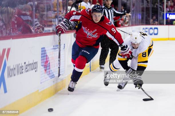 Dmitry Orlov of the Washington Capitals and Brian Dumoulin of the Pittsburgh Penguins battle for the puck in the third period at Capital One Arena on...
