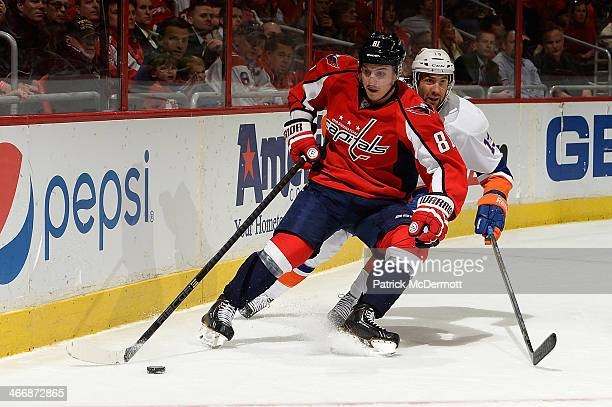 Dmitry Orlov of the Washington Capitals and Colin McDonald of the New York Islanders battle for the puck in the third period during an NHL game at...