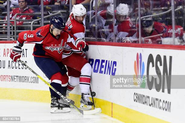 Dmitry Orlov of the Washington Capitals and Elias Lindholm of the Carolina Hurricanes battle for the puck in the second period during an NHL game at...