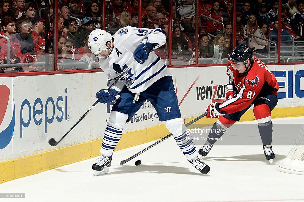 Dmitry Orlov #81 of the Washington Capitals battles for the puck against Joffrey Lupul #19 of the Toronto Maple Leafs in the third period during an NHL game at Verizon Center on January 10, 2014 in Washington, DC.