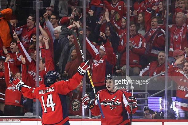 Dmitry Orlov of the Washington Capitals celebrates with teammate Justin Williams after scoring the gamewinning goal against the Minnesota Wild during...