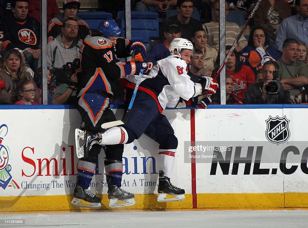 Dmitry Orlov #81 of the Washington Capitals hits Matt Martin #17 of the New York Islanders at the Nassau Veterans Memorial Coliseum on March 13, 2012 in Uniondale, New York.